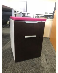 Pre-owned mobile box/file pedestal has white body with mahogany laminate fronts and a pink cushion top.