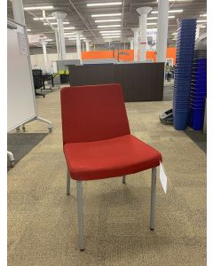 Angle view of Pre-owned HON armless side chair has red body and (4) metallic silver post legs. -B GRADE-