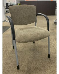Angle view of Pre-owned Highmark side chair has tan patterned upholstery with metallic silver frame with (4) post legs and black loop arms. -B GRADE-