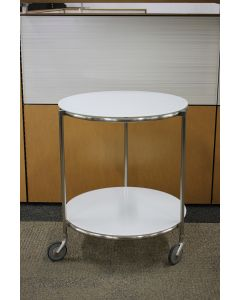 "Pre-owned two-tier round side table has frosted white surfaces. Features (3) chrome legs on casters. Dimensions: 20""W in diameter x 24""H."